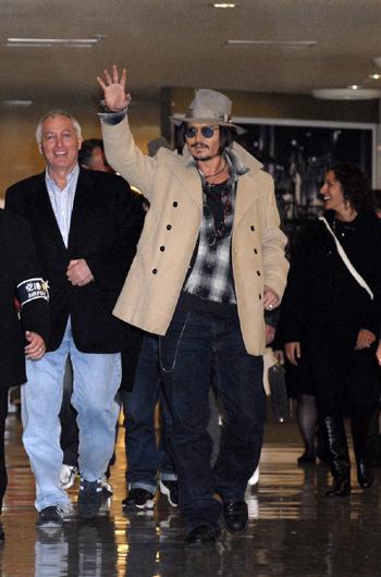 ベージュのPコート、ベージュの帽子、グレーのチェックのシャツに濃い青のジーンズを合わせたジョニー・デップらいしい服装で到着!